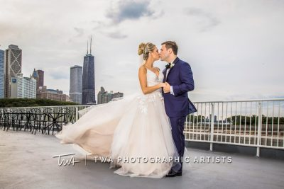 couple photographed in front of city skyline