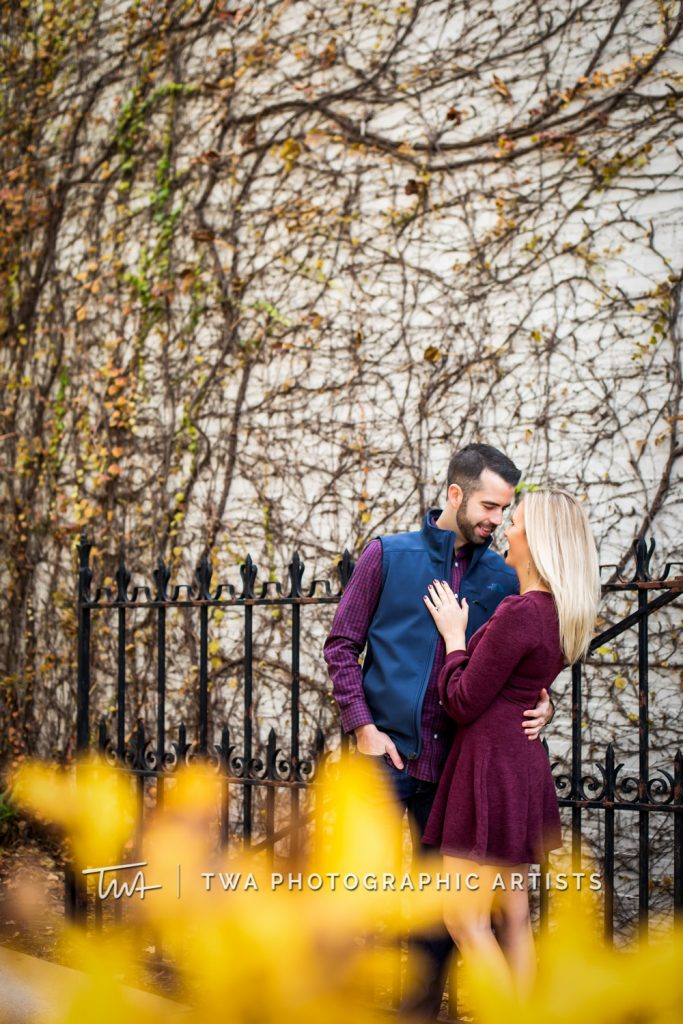 Couple posing in front of vine wall