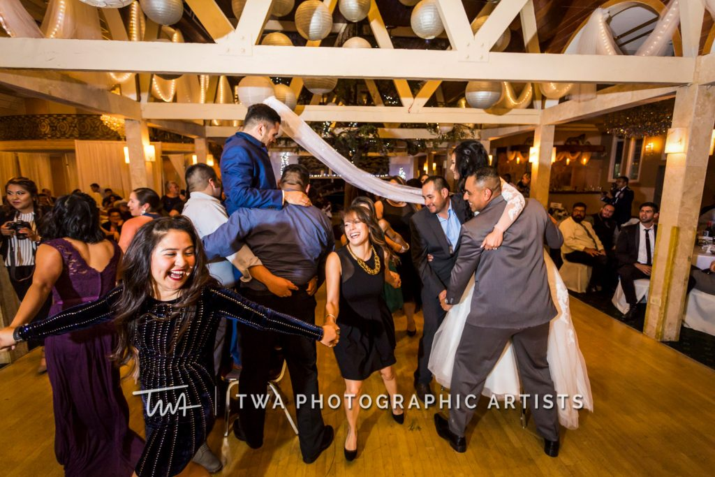 Couple being lifted in air at reception