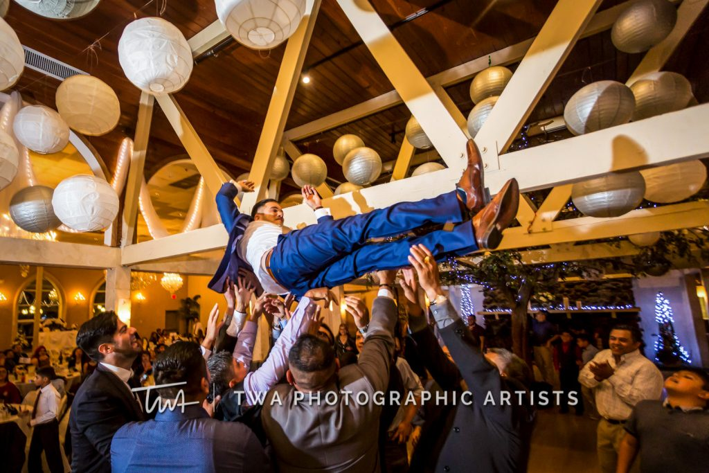Groom being lifted into the air during reception