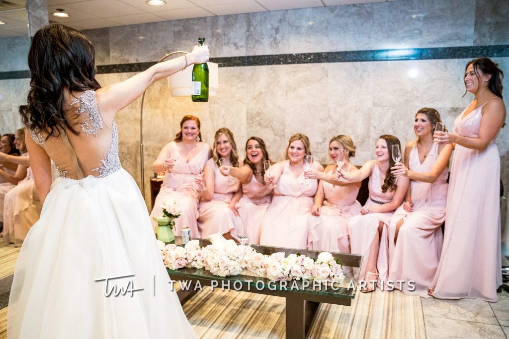 Bride popping champagne with bridesmaids